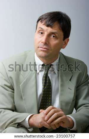 Fashionable businessman sitting and looking attentively