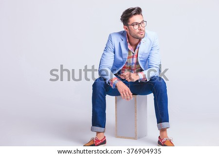 fashionable businessman wearing glasses posing while seated on box looking away from the camera in studio background