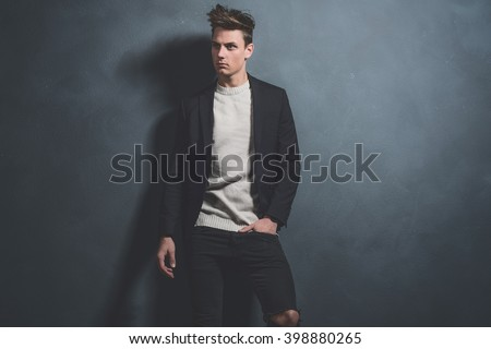 Fashionable casual young man wearing dark blue jacket and black jeans. Standing against gray wall.