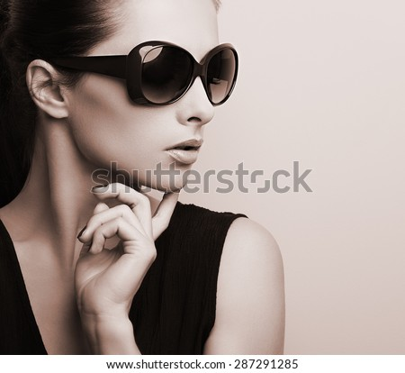 Fashionable chic female model profile in fashion sunglasses posing. Black and white color toned portrait - stock photo