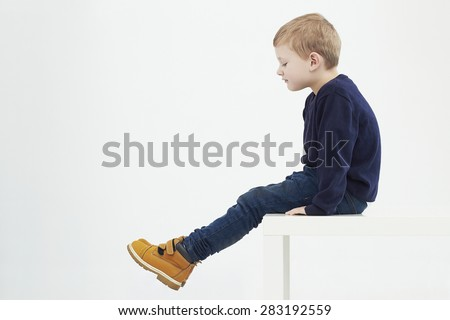 Fashionable child in yellow boots. fashion kids.children.little boy sitting on a table - stock photo