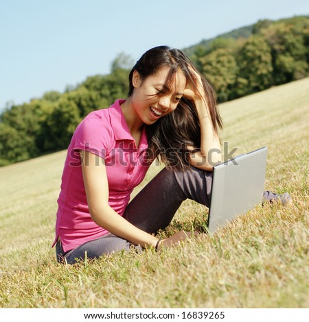 Fashionable Chinese girl working on laptop in a meadow.