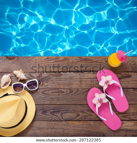 Fashionable clothes sunglasses, hat, flip-flops for beach holiday. Orange juice. Flat mock up for design. Top view. Summer vacation concept. - stock photo