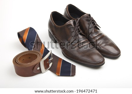Fashionable clothing accessories for business with a pair of classic lace-up brown leather shoes, coiled matching leather belt, striped blue, brown and gold tie and silver vintage pocket watch - stock photo