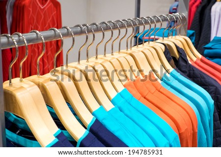 Fashionable clothing on hangers in shop