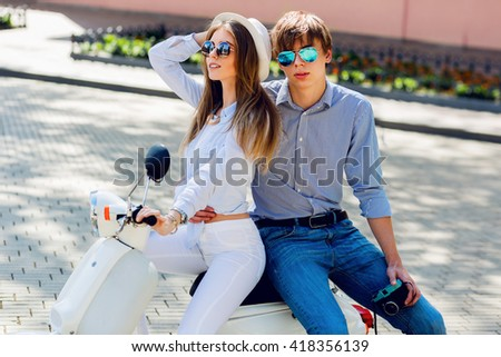 Fashionable  couple posing  on the street , wearing stylish casual clothes, bright sunglasses. Smiling  handsome guy and his pretty girlfriend hugging. Summer  or spring season.  - stock photo