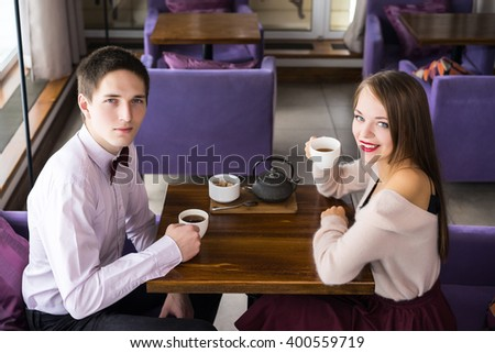 Fashionable couple sitting in the cafe and looking at camera