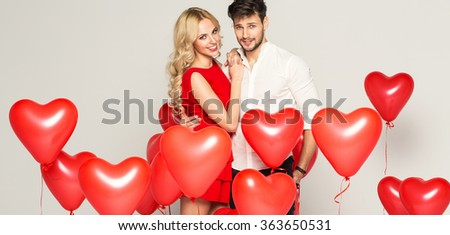 Fashionable couple with balloons heart hugging at each other  - stock photo