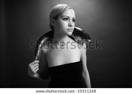 fashionable elegant girl with big fish on dark background - stock photo