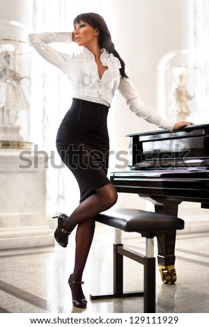 fashionable elegant woman at the piano - stock photo