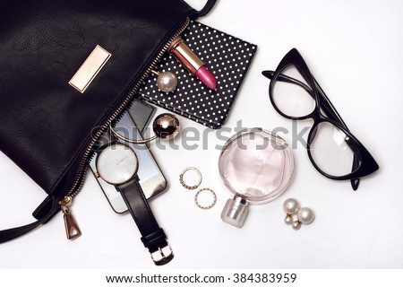 Fashionable female accessories watch glasses lipstick perfume and black bag. Overhead of essentials for any girl - stock photo