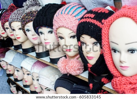 fashionable female knitted hats on mannequin heads at a beauty store