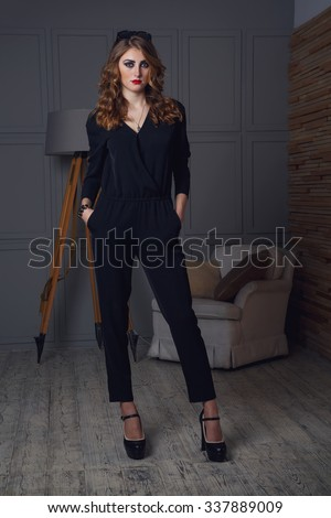 Fashionable female model posing. Fashion, photo of young magnificent woman. Girl posing in rooms studio. Beautiful brunette woman portrait in dark color. Sunglasses on top of a woman's head. - stock photo