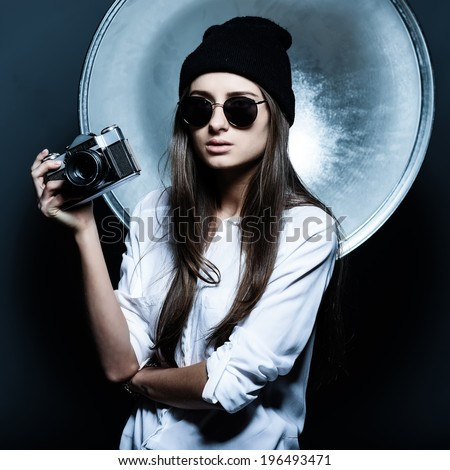 Fashionable girl hipster glasses and a hat in the studio - stock photo