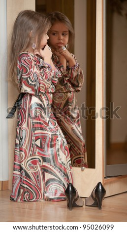 Fashionable girl in dress with mother's shoes. Reflection in the mirror. - stock photo