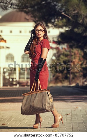 fashionable girl in red dress with bag crossing a city street - stock photo