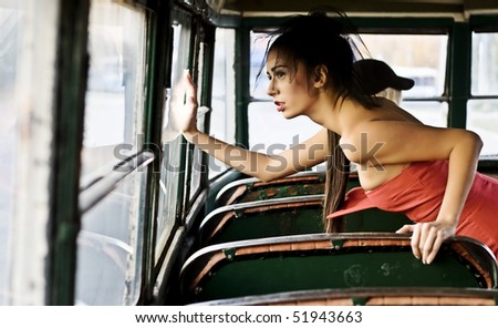 Fashionable girl looking trought bus window - stock photo