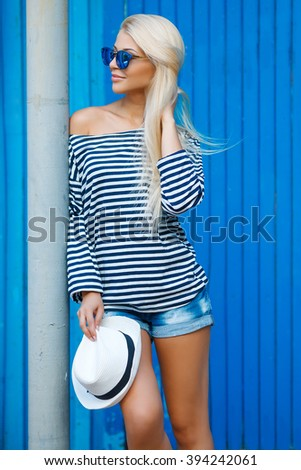 Fashionable girl photo. Marine style. beautiful blonde woman fresh face smiling and having fun on vacation in stripped t-short with blue wall on background. Summer. freedom. happiness. sea, shore - stock photo