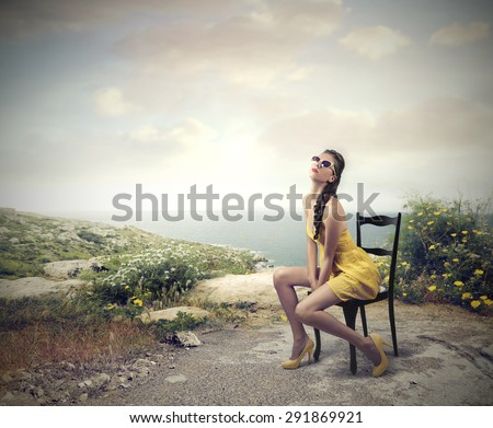 Fashionable girl sitting on a chair by the seaside