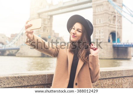Fashionable girl taking a selfie in London with Tower Bridge on background. She is wearing a camel coat and black hat and grimacing to the camera. Vintage filter applied. - stock photo
