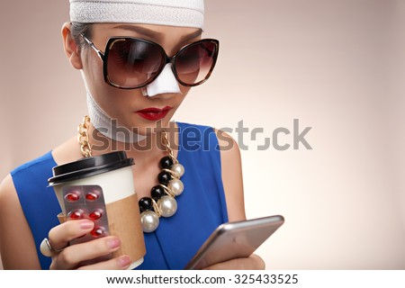 Fashionable girl with bandage on her face reading message in her smartphone - stock photo