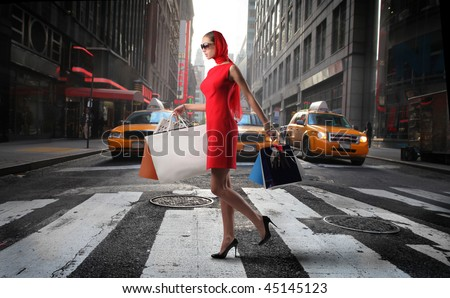 fashionable girl with shopping bags crossing a city street - stock photo