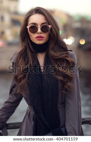 Fashionable glamorous girl with long curly hair wearing black dress, scarf, classy coat and sunglasses posing at city streets and looking at you or in camera. Fashion vogue style outdoor portrait
