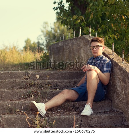 Fashionable guy sitting resting on the stairs - stock photo