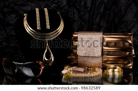 Fashionable handbag and golden jewelry, glasses on background. - stock photo