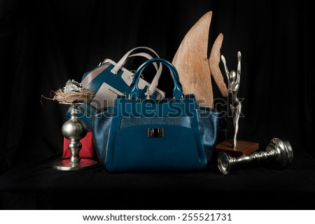 Fashionable handbag  with jewelry and different items for composition on black background.  - stock photo