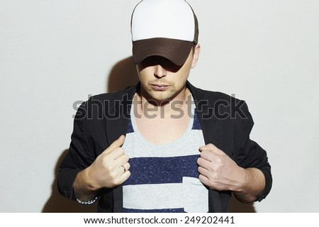 Fashionable Handsome Man in Cap. Stylish Boy in tracker hat. Casual Fashion.Young man - stock photo
