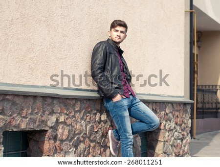 Fashionable handsome man model posing outdoors. Street fashion - stock photo
