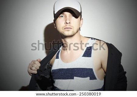 Fashionable Handsome Man. Stylish Boy in cap. Casual Fashion.posing Young man model - stock photo