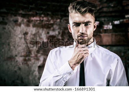 Fashionable handsome young man posing outdoor. Brick wall background. - stock photo