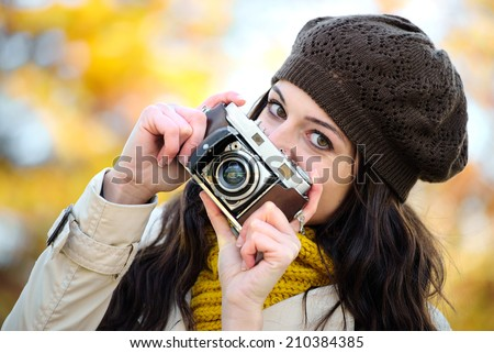 Fashionable happy woman taking photos with retro film camera in autumn season. Female beautiful photographer enjoying and having fun. Fashion girl wearing warm clothes. - stock photo