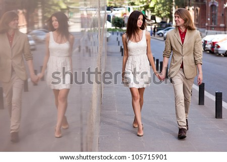 Fashionable happy young couple of a handsome man with long hair and attractive woman walking on the street holding hands - stock photo