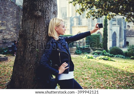Fashionable hipster girl is taking photo with front camera of smart phone for chat in social network with her friends. Woman with cool style is posing, while is making self portrait on cell telephone