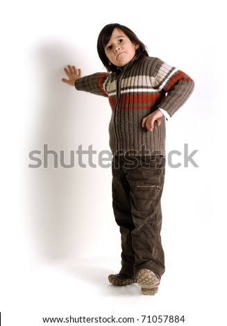 Fashionable kid standing against white wall - stock photo