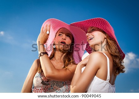 Fashionable ladies discuss and admire in outdoors - stock photo