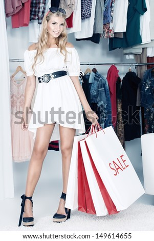 Fashionable lady standing with a lot of shopping bags in a store. - stock photo