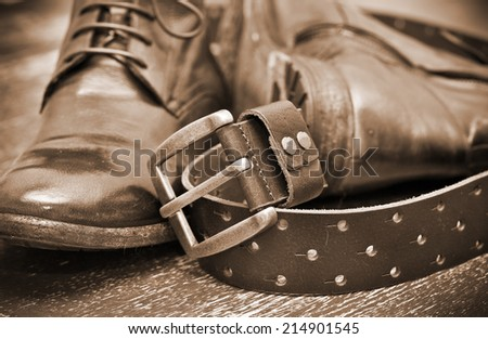 Fashionable leather boots and brown leather belt with gold buckle. Vintage style. Handmade. Autumn and spring shoes. Photo toning in sepia - stock photo
