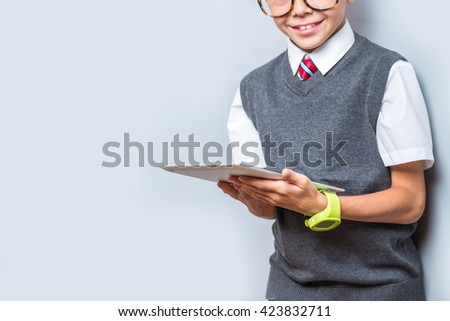 Fashionable little boy in glasses using tablet, focus on hands. Stylish kid in suit. Fashion children. Business boy - stock photo