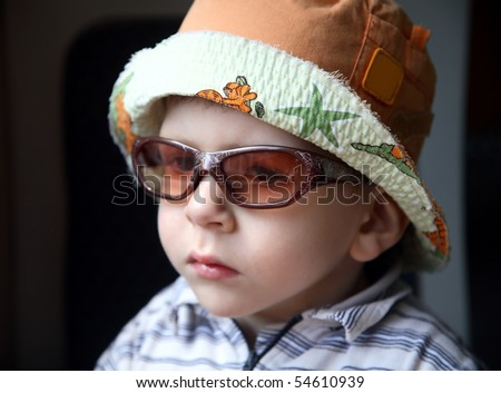 Fashionable little boy with sunglasses and hat