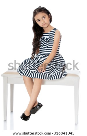 Fashionable little dark-haired girl dressed in a striped summer dress sat down on a white couch, dangling with his feet-Isolated on white background