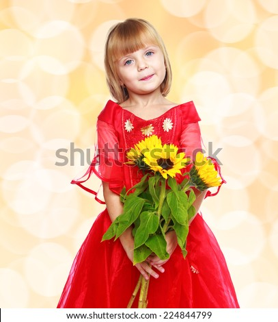 Fashionable little girl in a red dress and a bouquet of sunflowers.Happiness, winter holidays, new year, and childhood. - stock photo