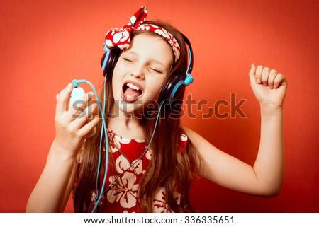 Fashionable little girl listening to music on headphones - stock photo