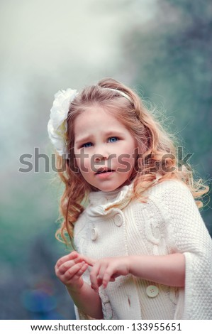 Fashionable little model girl on white stylish wear with curly hair and flower