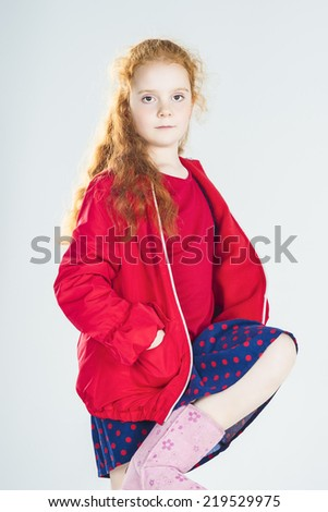 Fashionable Little Red-Haired Caucasian Girl In Studio. Against White Background. Vertical Image - stock photo