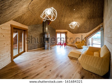 Fashionable living room with wooden floor and walls and straw ceiling - stock photo