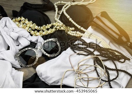 Fashionable luxury accessories set,  Summer clothes, sunglasses, necklaces. (Selective focused), (Lighting Effect Processed)